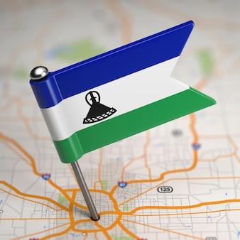 Mała flaga królestwa lesotho na tle mapy z selektywną ostrością.