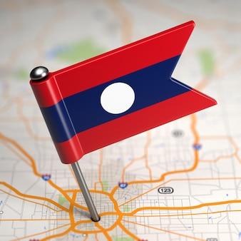 Mała flaga laotańskiej republiki ludowo-demokratycznej na tle mapy z selektywną ostrością.