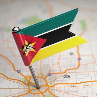 Mała flaga mozambiku na tle mapy z selektywną ostrością.