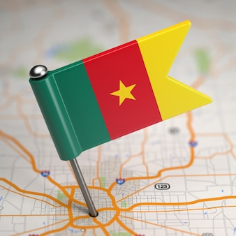 Mała flaga republiki kamerunu na tle mapy z selektywną ostrością.