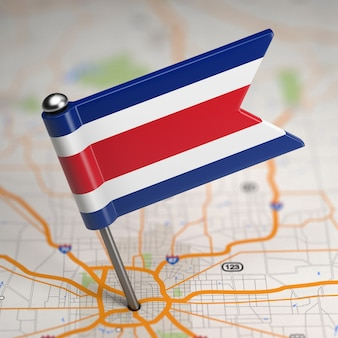 Mała flaga republiki kostaryki na tle mapy z selektywną fokusem.