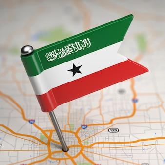 Mała flaga republiki somalilandu na tle mapy z selektywną fokusem.