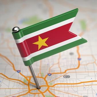 Mała flaga republiki surinamu na tle mapy z selektywną ostrością.