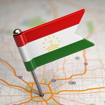 Mała flaga republiki tadżykistanu na tle mapy z selektywną fokusem.