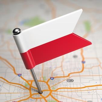 Mała flaga rzeczypospolitej polskiej na tle mapy z selektywną ostrością.