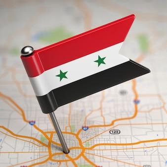 Mała flaga syryjskiej republiki arabskiej na tle mapy z selektywną ostrością.