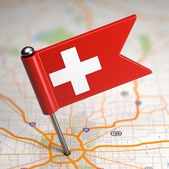 Mała flaga szwajcarii na tle mapy z selektywną ostrością.
