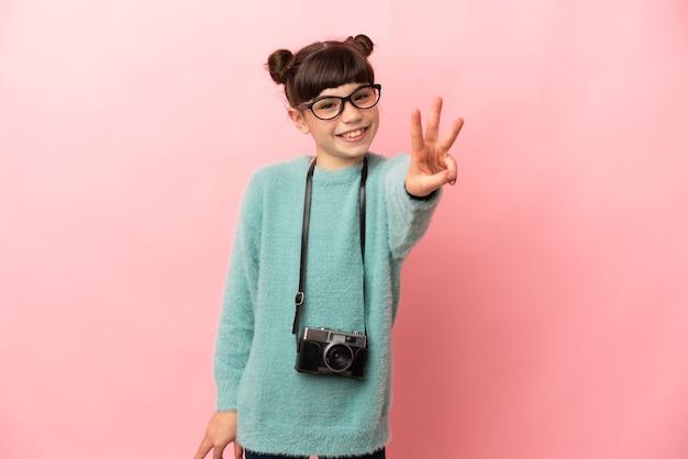 Mała fotografka odizolowana na różowym tle szczęśliwa i licząca trzy palcami