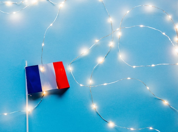 Mała francuska flaga i bajkowe światła na niebieskim tle