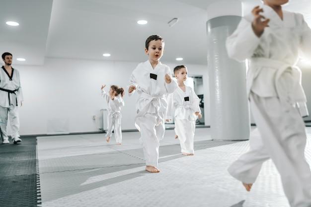 Mała grupa dzieci trenujących na zajęciach taekwondo. wszyscy ubrani w doboki. białe tło.