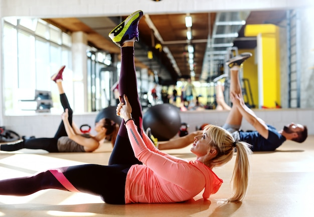 Mała grupa ludzi o zdrowych nawykach robi ćwiczenia rozciągające na podłodze siłowni. selekcyjna ostrość na blondynki kobiecie. w lustrze w tle.
