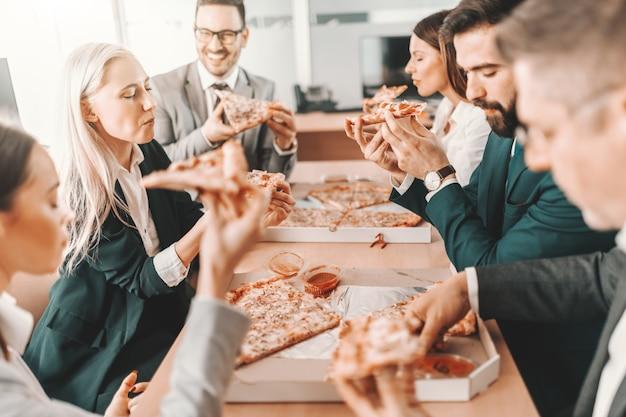 Mała grupa szczęśliwych kolegów w wizytowych strojach rozmawiających i jedzących razem pizzę na lunch. zamiast starać się być najlepszym w zespole, bądź najlepszy dla zespołu.
