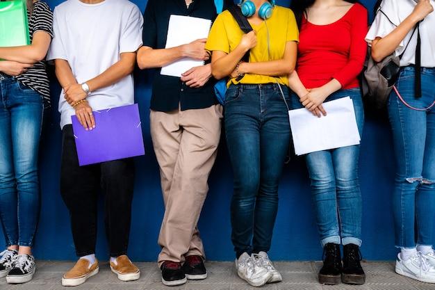 Mała grupa uczniów szkół średnich stoi oparta o niebieską ścianę powrót do szkoły edukacja