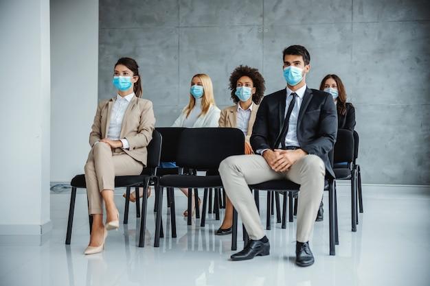 Mała grupa wielokulturowych biznesmenów z maskami na twarzach siedząca na seminarium podczas koronawirusa