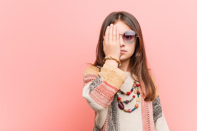 Mała hipis dziewczyna ma zabawę zakrywa połówkę twarzy z palmą.
