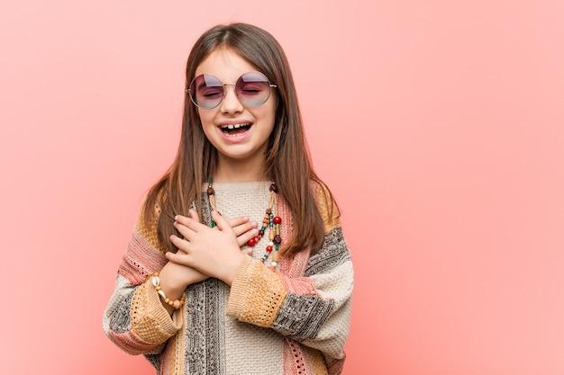 Mała hipis dziewczyna śmia się utrzymujący ręki na sercu, pojęcie szczęście.