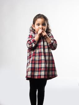 Mała indyjska dziewczynka prosi o milczenie lub milczenie z palcem wskazującym na ustach