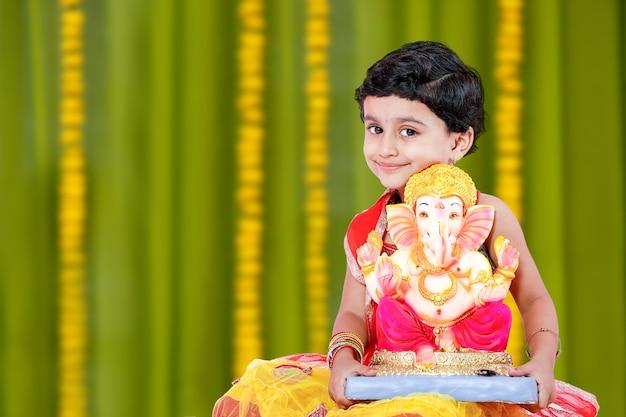Mała indyjska dziewczynka z lordem ganesha i modląca się, indyjski festiwal ganesh