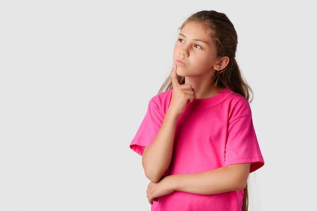 Mała inteligentna dziewczyna myśli o czymś i patrzy w lewo. piękna dziewczyna marząca o swojej przyszłości decyduje, co robić