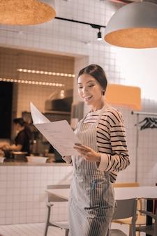 Mała kafeteria. promieniejąca kobieta sukcesu, patrząc na menu swojej małej przytulnej kafeterii
