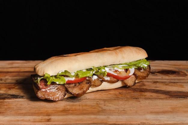 Mała kanapka z mięsem i warzywami na drewnianym stole na czarnym tle
