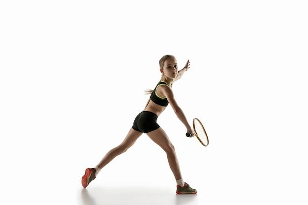 Mała kaukaska dziewczynka gra w tenisa na białej ścianie