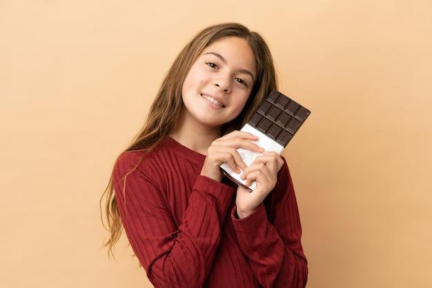 Mała kaukaska dziewczynka na beżowym tle bierze tabliczkę czekolady i jest szczęśliwa