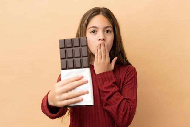 Mała kaukaska dziewczynka na beżowym tle bierze tabliczkę czekolady i jest zaskoczona