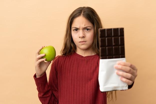 Mała kaukaska dziewczynka na beżowym tle bierze w jedną rękę tabliczkę czekolady, a w drugiej jabłko