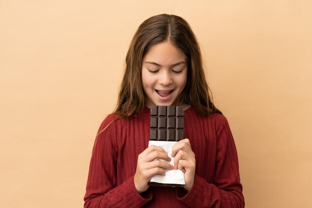 Mała kaukaska dziewczynka na beżowym tle jedząca czekoladową tabliczkę