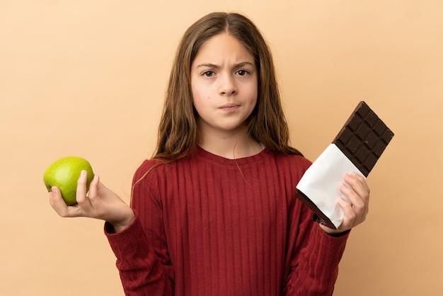 Mała kaukaska dziewczynka na beżowym tle ma wątpliwości, biorąc w jedną rękę tabliczkę czekolady, a w drugiej jabłko