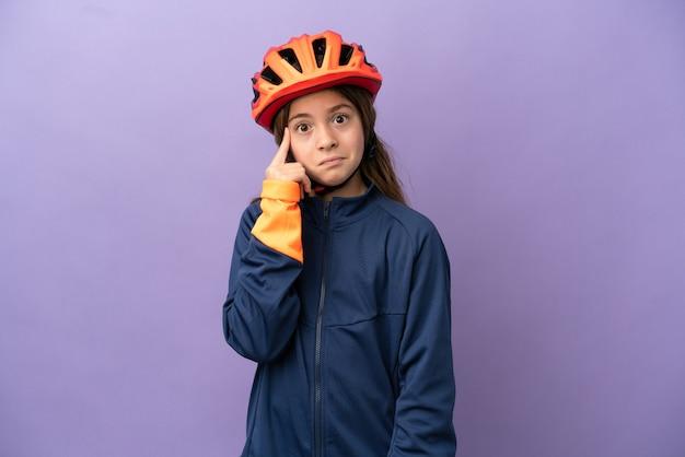 Mała kaukaska dziewczynka na fioletowym tle myśląca o pomyśle