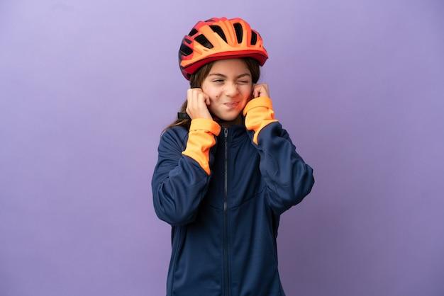 Mała kaukaska dziewczynka na fioletowym tle sfrustrowana i zakrywająca uszy