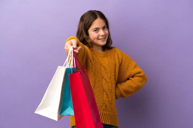Mała kaukaska dziewczynka na fioletowym tle trzymająca torby na zakupy i dająca je komuś