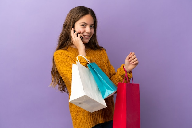 Mała kaukaska dziewczynka na fioletowym tle trzymająca torby na zakupy i dzwoniąca do przyjaciela telefonem komórkowym