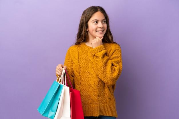 Mała kaukaska dziewczynka na fioletowym tle trzymająca torby na zakupy i myśląca