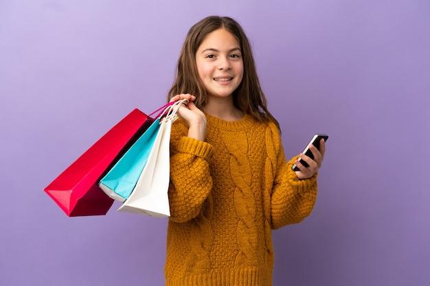 Mała kaukaska dziewczynka na fioletowym tle trzymająca torby na zakupy i pisząca wiadomość telefonem komórkowym do przyjaciela