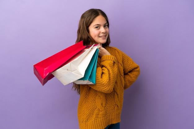 Mała kaukaska dziewczynka na fioletowym tle trzymająca torby na zakupy i uśmiechnięta