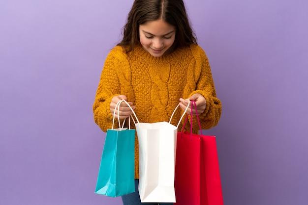 Mała kaukaska dziewczynka na fioletowym tle trzymająca torby na zakupy i zaglądająca do środka