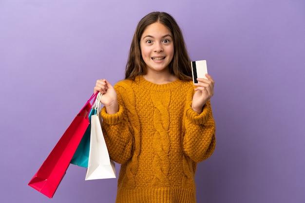 Mała kaukaska dziewczynka na fioletowym tle trzymająca torby na zakupy i zaskoczona