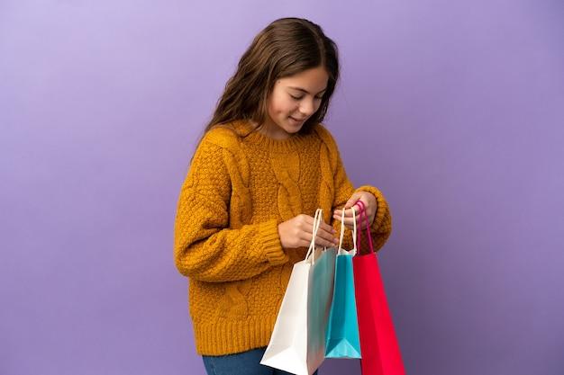Mała kaukaska dziewczynka na fioletowym tle trzymająca torby na zakupy
