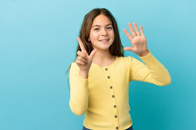 Mała kaukaska dziewczynka na niebieskim tle, licząc siedem palcami