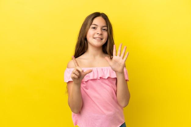 Mała kaukaska dziewczynka na żółtym tle licząca siedem palcami