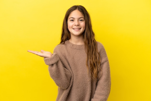 Mała kaukaska dziewczynka na żółtym tle trzymająca wyimaginowaną copyspace na dłoni, aby wstawić reklamę