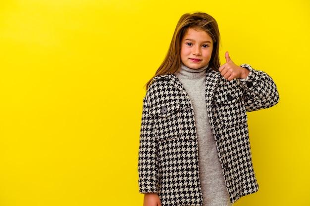 Mała kaukaska dziewczynka na żółtym tle uśmiecha się i podnosi kciuk w górę
