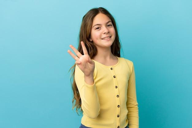 Mała kaukaska dziewczynka odizolowana na niebieskim tle szczęśliwa i licząca trzy palcami