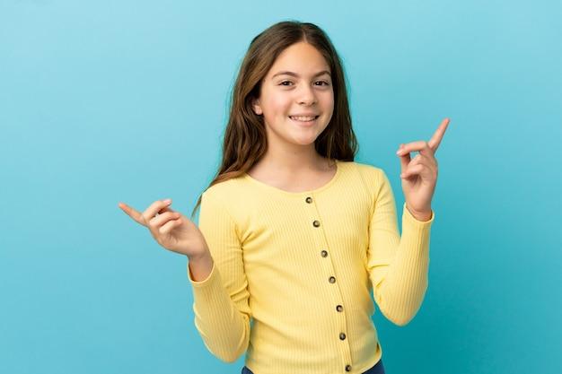 Mała kaukaska dziewczynka odizolowana na niebieskim tle, wskazując palcem na boki i szczęśliwa