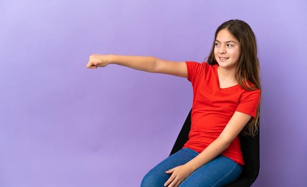 Mała kaukaska dziewczynka siedząca na krześle na białym tle na fioletowym tle dająca gest kciuka w górę