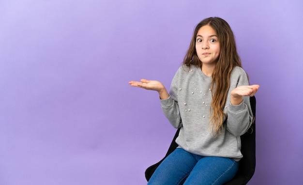 Mała kaukaska dziewczynka siedząca na krześle na białym tle na fioletowym tle, mająca wątpliwości podczas podnoszenia rąk
