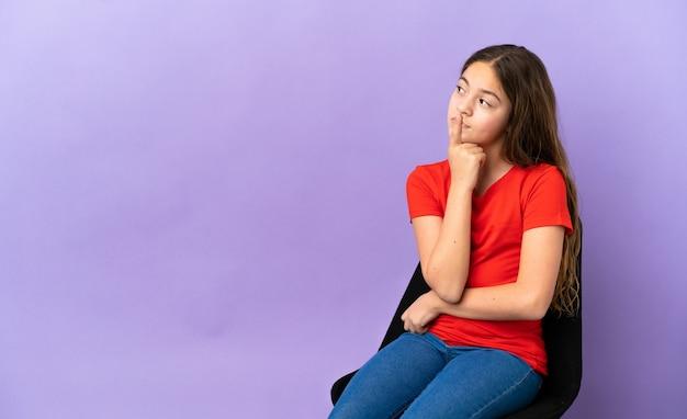 Mała kaukaska dziewczynka siedzi na krześle na białym tle na fioletowym tle, mając wątpliwości, patrząc w górę